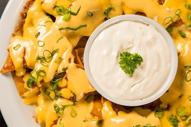 Chipsy nachos z serem cheddar i różnorodne dipy na talerzu.