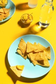 Chipsy nachos z sosem serowym na niebieskim talerzu na żółtym tle