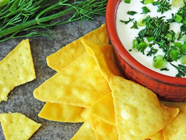 Chipsy nachos z sosem śmietanowym i zieleniną.