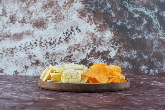 Chipsy serowe i chipsy ziemniaczane w talerzu, na marmurowym stole.