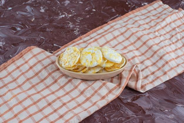 Chipsy serowe na talerzu na ściereczce, na marmurowym stole.