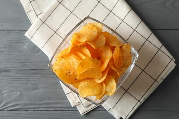 Chipsy, serwetka na szarym drewnie, miejsca na tekst. widok z góry
