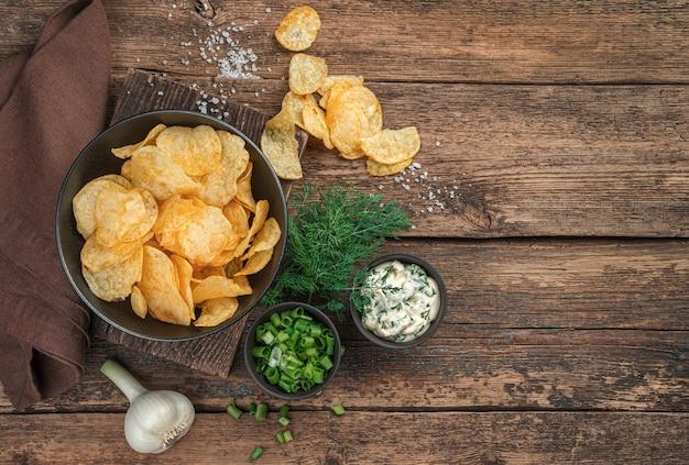 Chipsy, świeże zioła i sos na drewnianym tle. widok z góry, kopia przestrzeń.