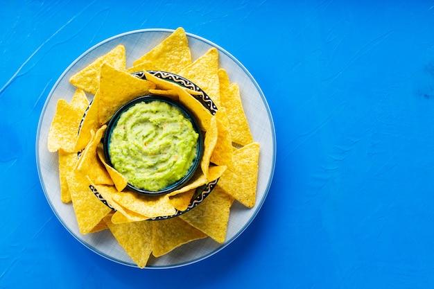 Chipsy Tortilla I Sos Guacamole Na Niebieskim Tle. Guacamole Z Chipsami Kukurydzianymi Na Talerzu. Skopiuj Miejsce. Widok Z Góry Premium Zdjęcia