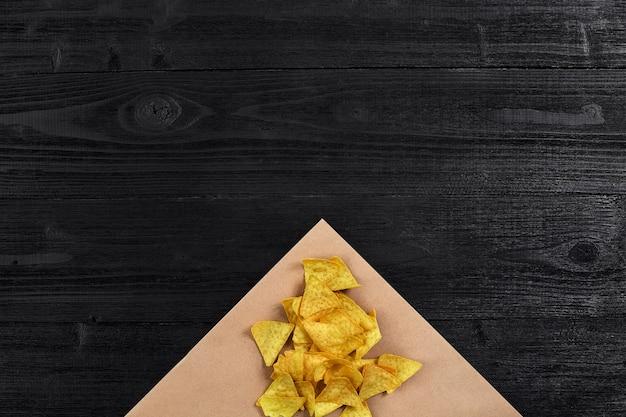 Chipsy tortilla na czarnym drewnianym stole z widokiem na blat