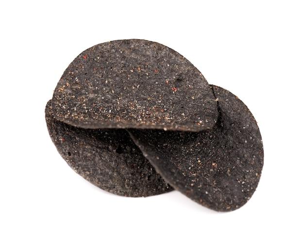 Chipsy ziemniaczane czarne na białym tle. czarne chipsy z węglem aktywnym i czerwoną papryką.