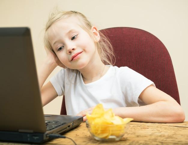 Chipsy ziemniaczane i dziewczyna przed laptopem.