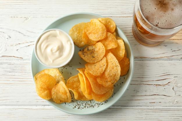 Chipsy ziemniaczane i szklanka piwa. przekąski do piwa, sos na białym drewnie, miejsce na tekst. widok z góry