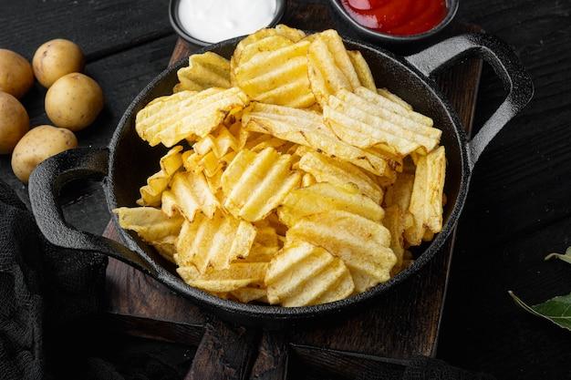Chipsy ziemniaczane na czarnym tle drewnianych