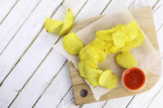 Chipsy ziemniaczane na drewnianej tacy na białym stole