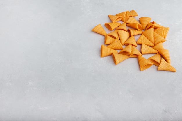Chipsy ziemniaczane rozłożone na białym tle w górnym rogu.