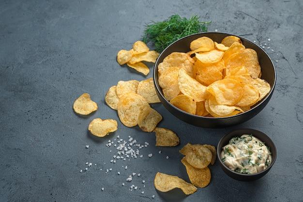 Chipsy ziemniaczane, sos, koperek na szarym tle. przystawka do piwa.