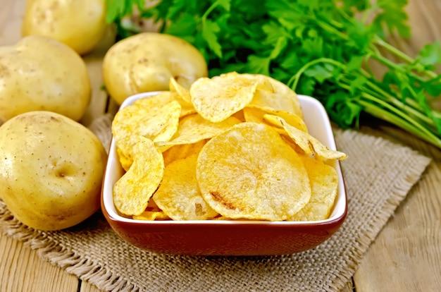 Chipsy ziemniaczane w glinianej misce na serwetce z juty, świeże ziemniaki, pietruszka na tle drewnianych desek