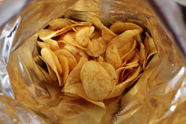Chipsy ziemniaczane w opakowaniu wewnątrz. przekąski w paczce z bliska.