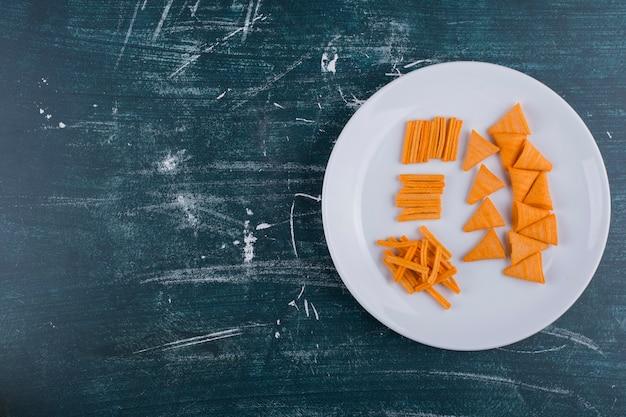 Chipsy ziemniaczane w sosie pomidorowym w białym talerzu, widok z góry