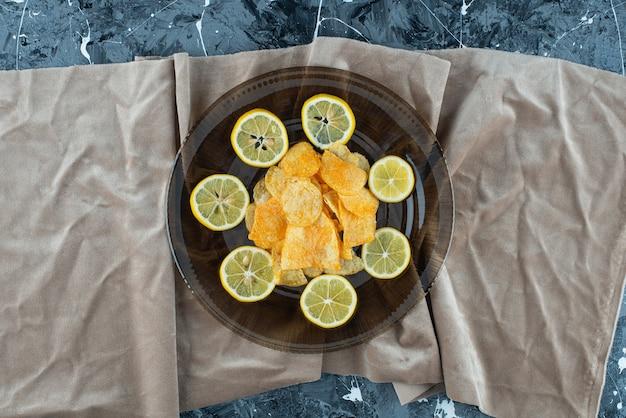 Chipsy ziemniaczane w szklanej płytce na kawałkach tkaniny na marmurze.