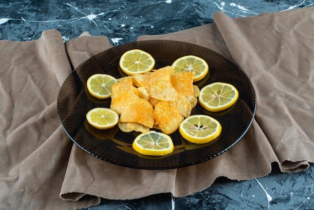 Chipsy ziemniaczane w szklanej płytce na kawałkach tkaniny, na tle marmuru.
