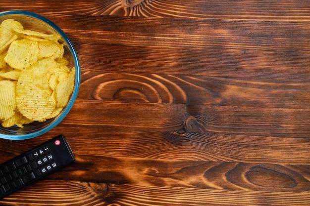 Chipsy ziemniaczane w szklanym naczyniu obok pilota telewizora na opalanym drewnem z miejsca na kopię. widok z góry.