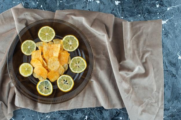 Chipsy ziemniaczane w szklanym talerzu na kawałkach tkaniny, na marmurowym stole.