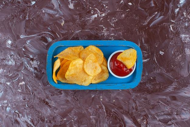 Chipsy ziemniaczane z keczupem w drewnianej tablicy na marmurze.