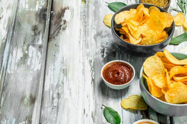 Chipsy ziemniaczane z różnymi sosami. na rustykalnym tle.