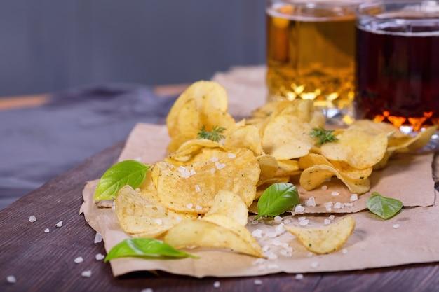 Chipsy ziemniaczane z solą i zielenią na stole w pubie