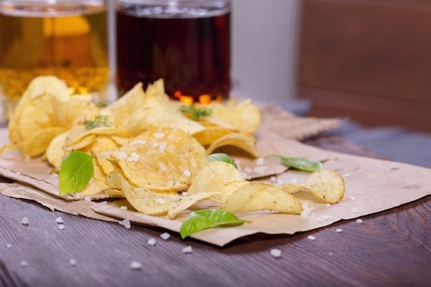 Chipsy ziemniaczane z solą i zielenią z piwem na stole w pubie
