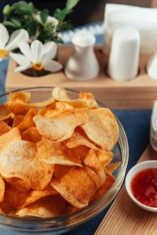 Chipsy ziemniaczane z sosem na stole. sosy domowe