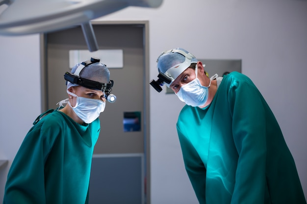 Chirurdzy noszący chirurgiczne lupy podczas wykonywania operacji