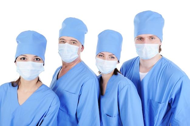 Chirurdzy w niebieskich mundurach medycznych stojących w kolejce