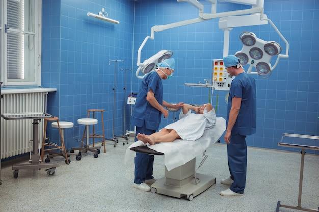 Chirurdzy wchodzący w interakcje z pacjentem podczas operacji
