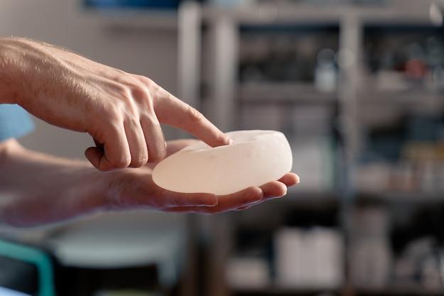 Chirurg dotyka i ściska silikonowe implanty w celu kontroli jakości. powiększanie piersi i podnoszenie piersi