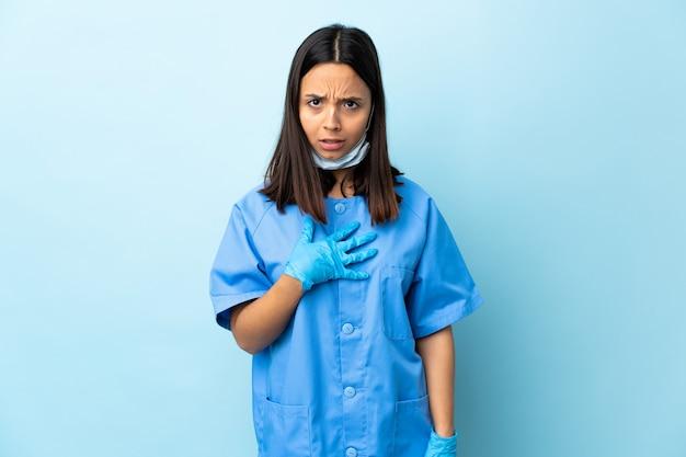 Chirurg kobieta nad odosobnioną błękit ścianą wskazuje do siebie