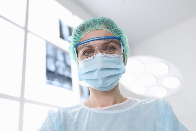 Chirurg kobieta w sterylnym garniturze na sali operacyjnej