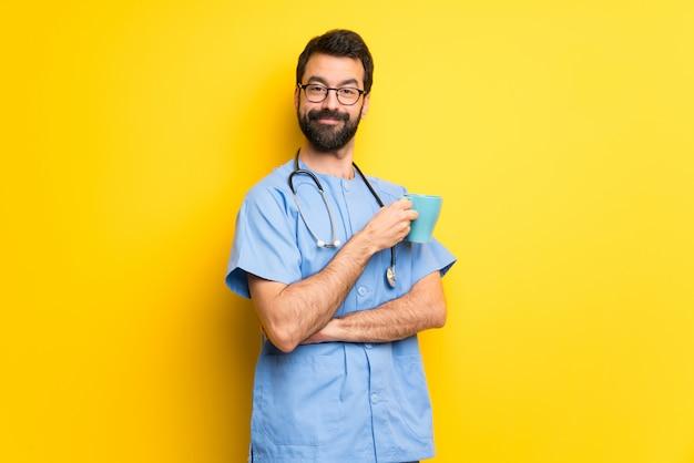 Chirurg lekarz mężczyzna trzyma filiżankę gorącej kawy