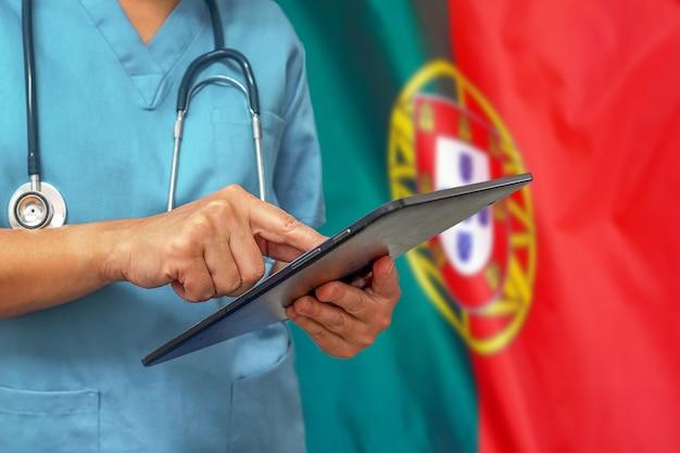 Chirurg lub lekarz za pomocą cyfrowego tabletu na tle flagi portugalii