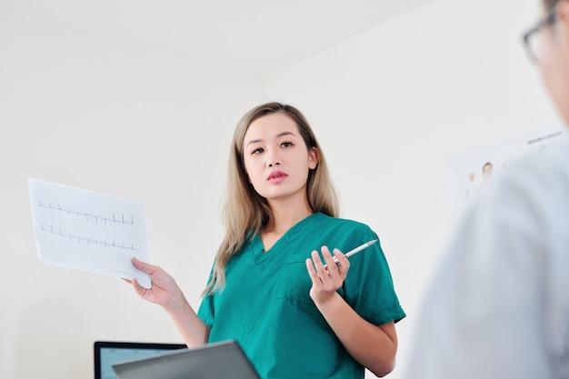 Chirurg omawiający kardiogram pacjenta