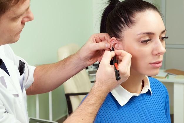 Chirurg plastyczny bada ucho pacjenta przed operacją plastyczną i rysowaniem linii