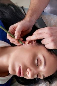 Chirurg plastyczny bada ucho pacjenta przed operacją plastyczną