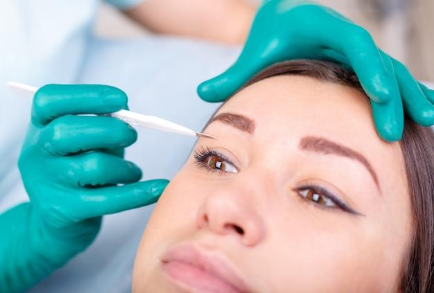 Chirurg plastyczny egzamininuje żeńskiego klienta w klinice przed chirurgią plastyczną