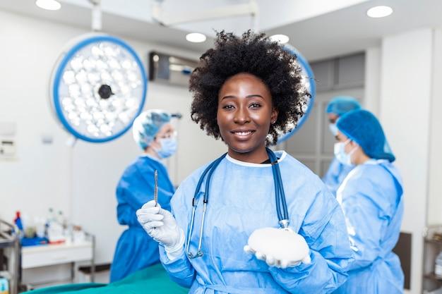 Chirurg plastyczny kobieta trzyma silikonowe implanty piersi we wnętrzu sali operacyjnej