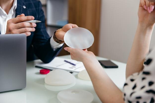 Chirurg plastyczny pokazuje pacjentce próbki implantów piersi i opowiada o jej przyszłej operacji