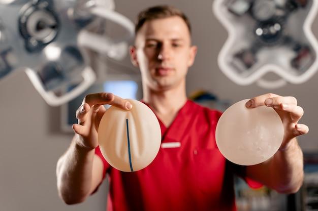 Chirurg pokazuje różne rodzaje implantów silikonowych. operacja powiększania piersi.