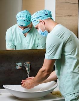 Chirurg przed operacją myje ręce środkiem antyseptycznym
