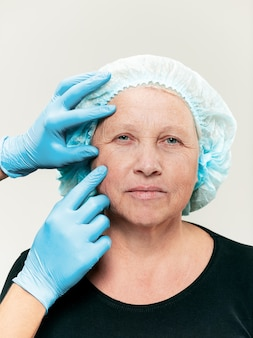 Chirurg robi kontrolę skóry kobiety w średnim wieku przed operacją plastyczną