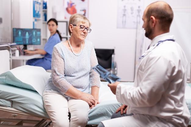 Chirurg rozmawiający o leczeniu ze starszą kobietą w gabinecie