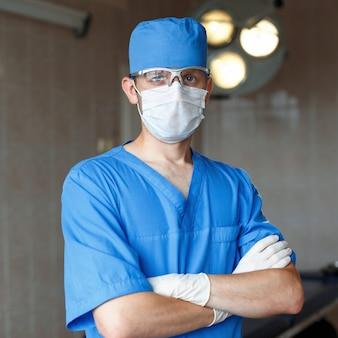 Chirurg w niebieskim mundurze, okularach i kapeluszu stoi na sali operacyjnej
