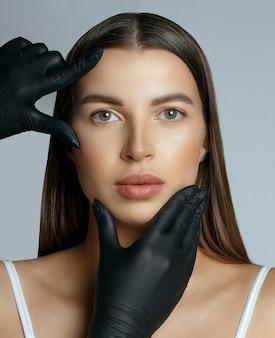 Chirurg w rękawiczkach sprawdzający skórę kobiecej twarzy przed operacją estetyczną