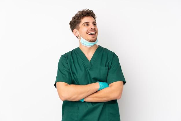 Chirurg w zielonym mundurze na białej ścianie szczęśliwy i uśmiechnięty