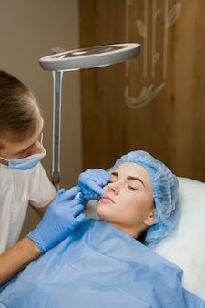 Chirurg wykonuje operację plastyczną plastyki ust za pomocą wypełniacza w klinice medycznej dla atrakcyjnej dziewczyny